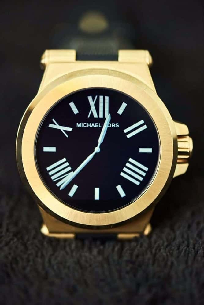 Michael Kors gold smartwatch with black watch face.