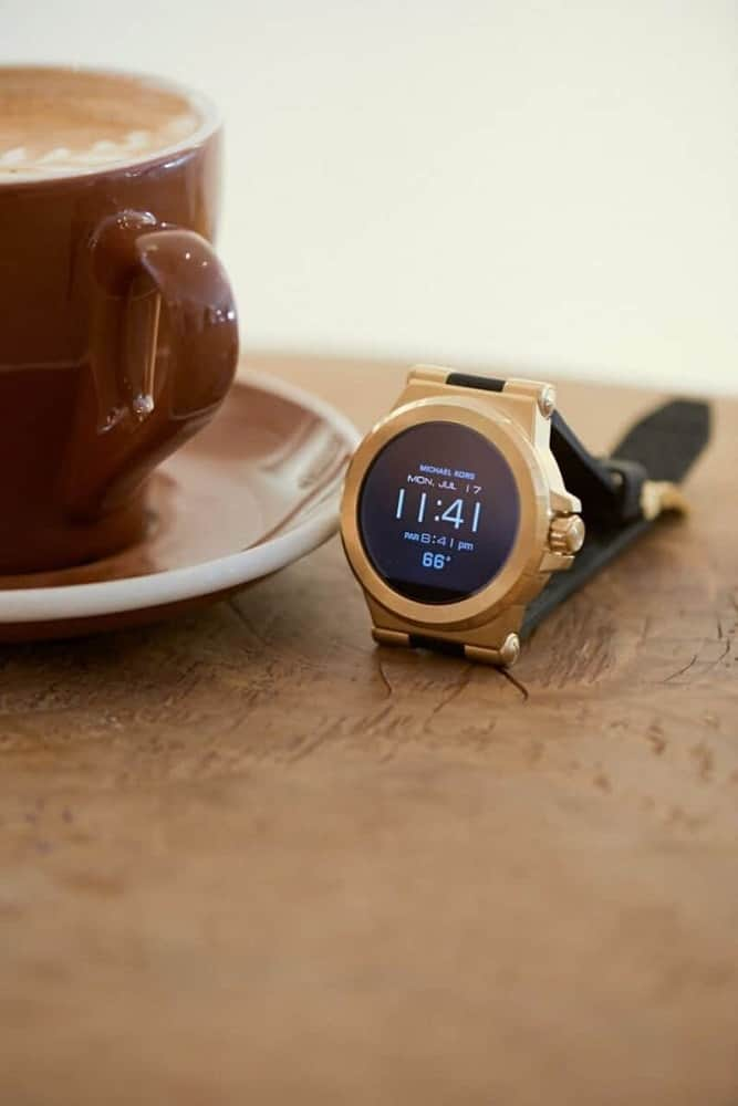 Michael Kors gold smartwatch on a wooden table.