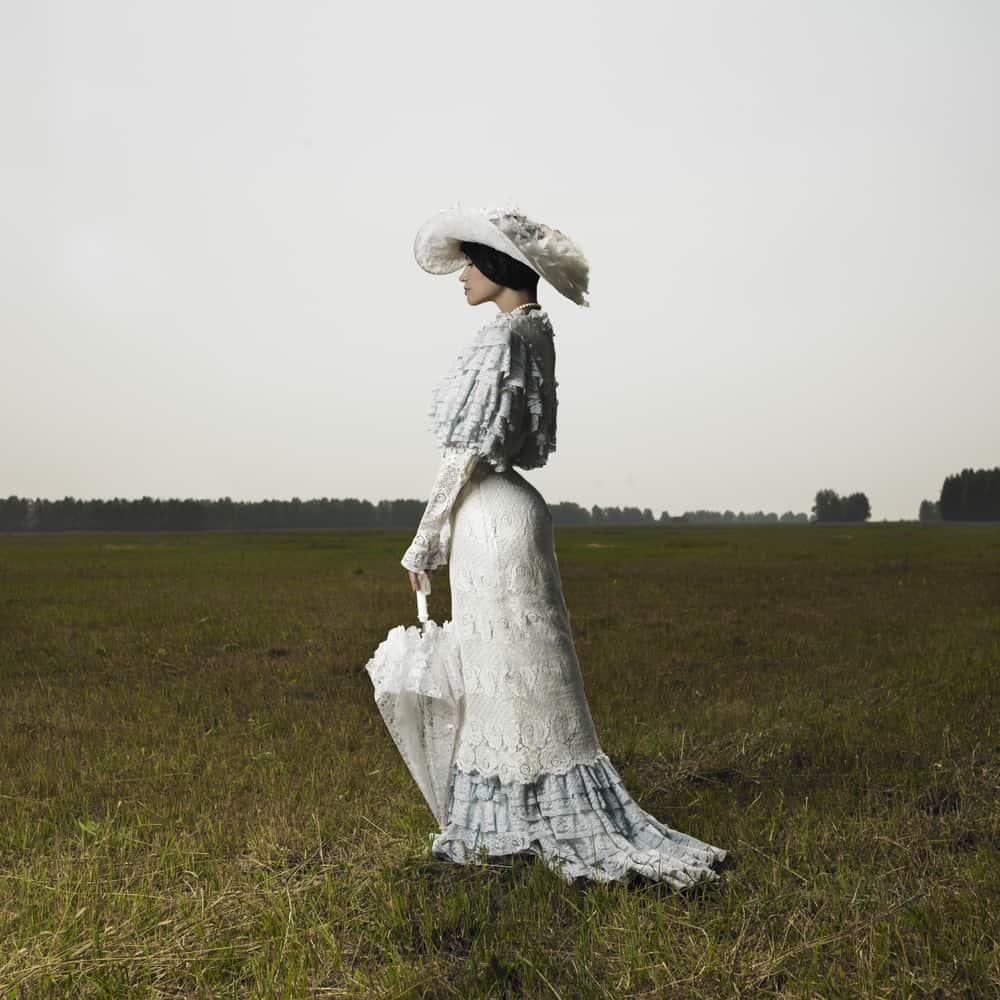 Woman wearing a Victorian dress with matching hat and umbrella.