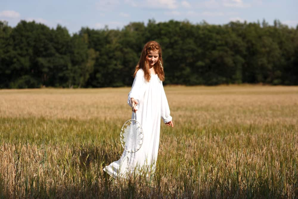 A girl in the middle of a field wearing a white peasant dress and holding a dream catcher.