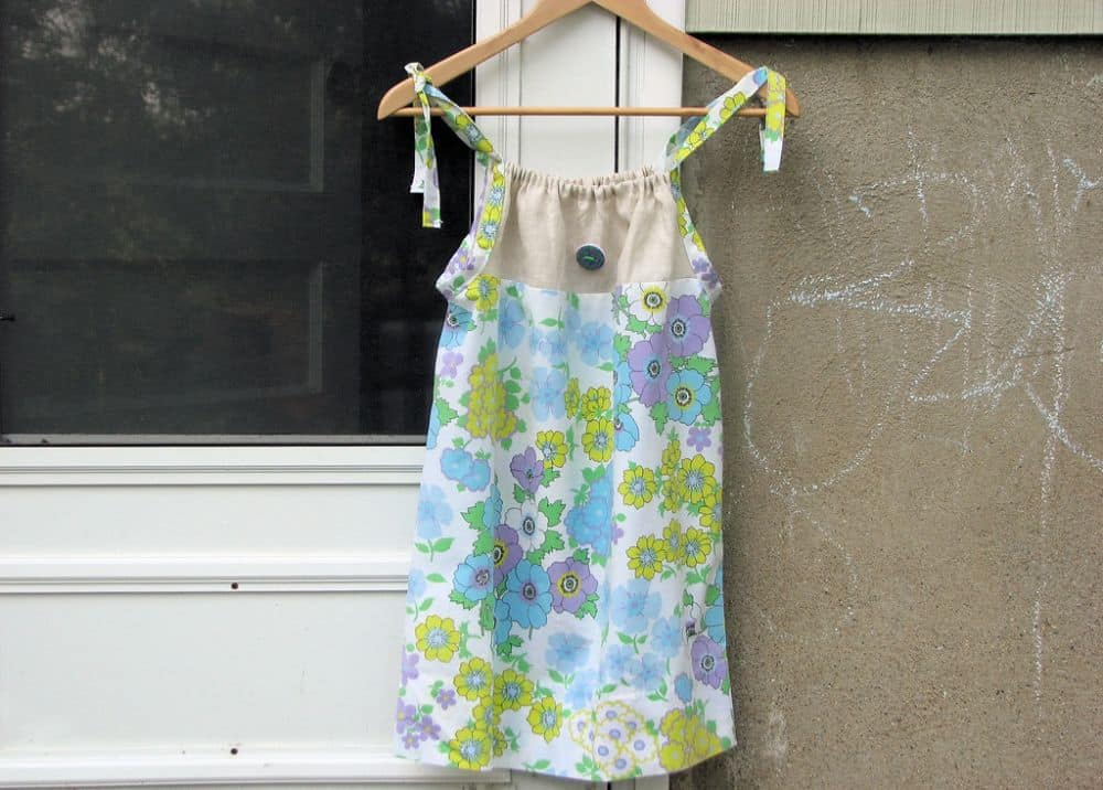 A pillowcase dress with floral print in a hanger.