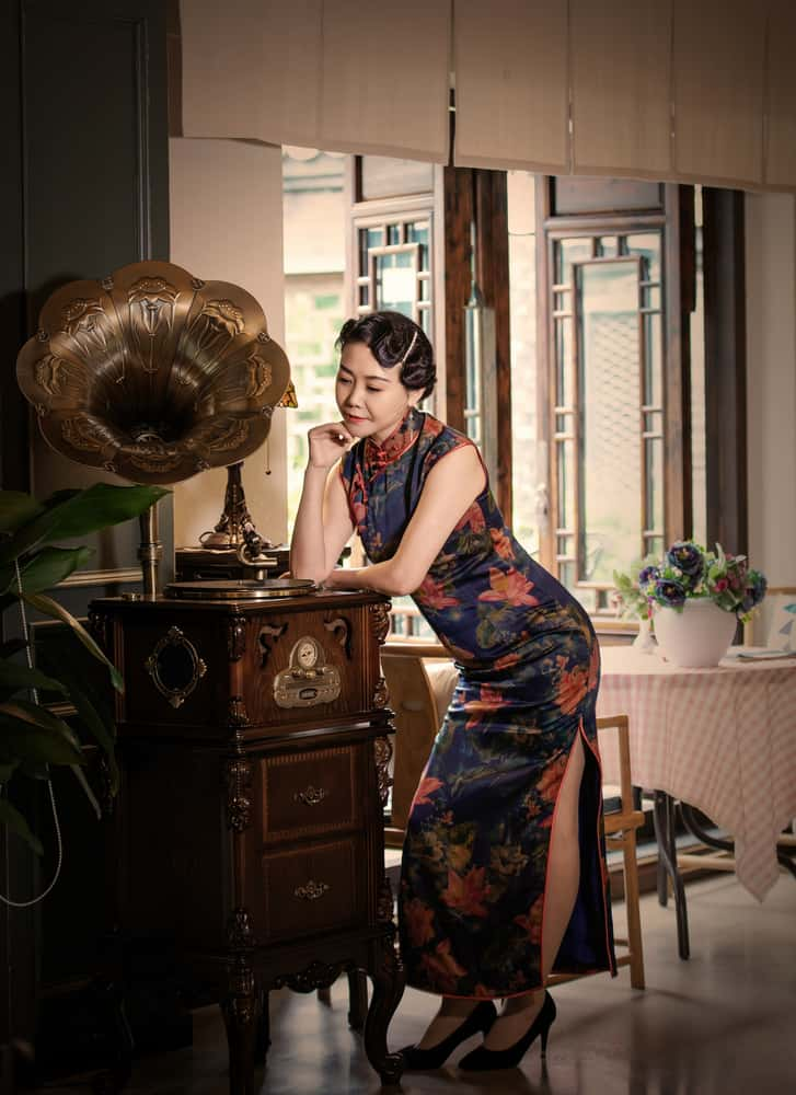 Woman in a qipao dress standing next to an ancient phonograph.