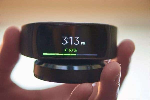 A close look at the Samsung Gear Fit 2 Smartwatch that is charging to show the size in proximity to hand.