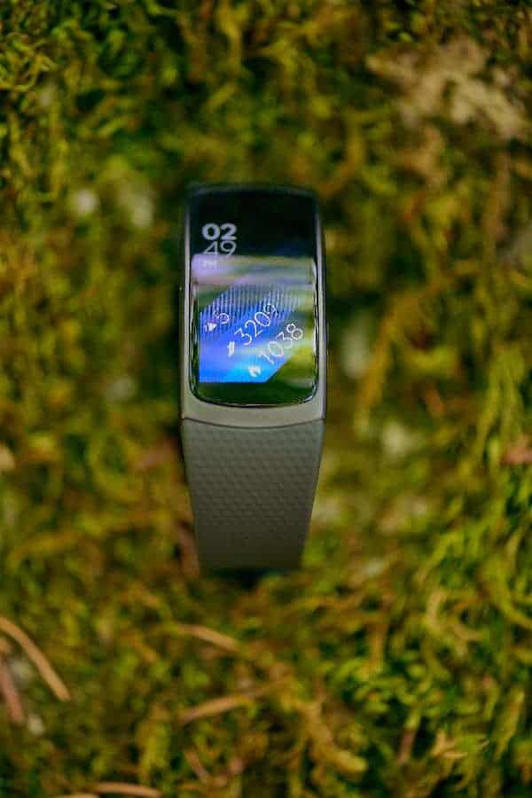 A close look at the Samsung Gear Fit 2 Smartwatch on a grass lawn.