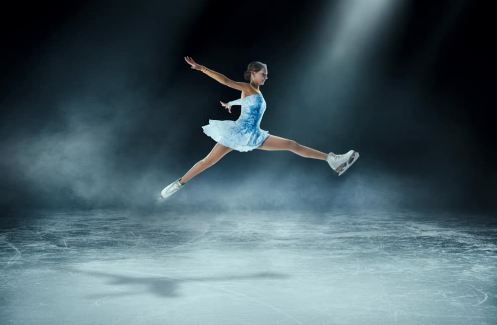 A girl figure skating in an ice arena.