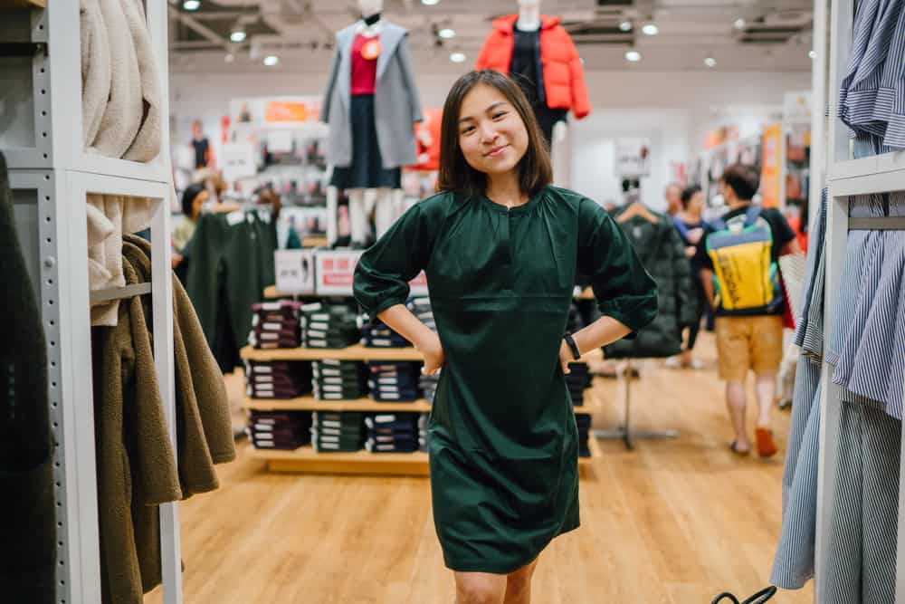 A woman tries on a green smock dress in a fashion store.
