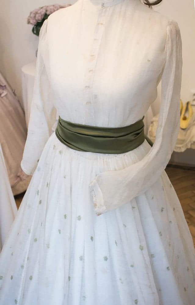 A close look at a white dress with a green sash belt on display.