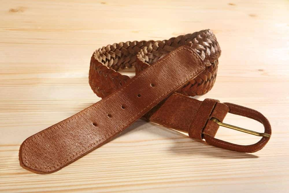 A close look at a brown leather braided belt.