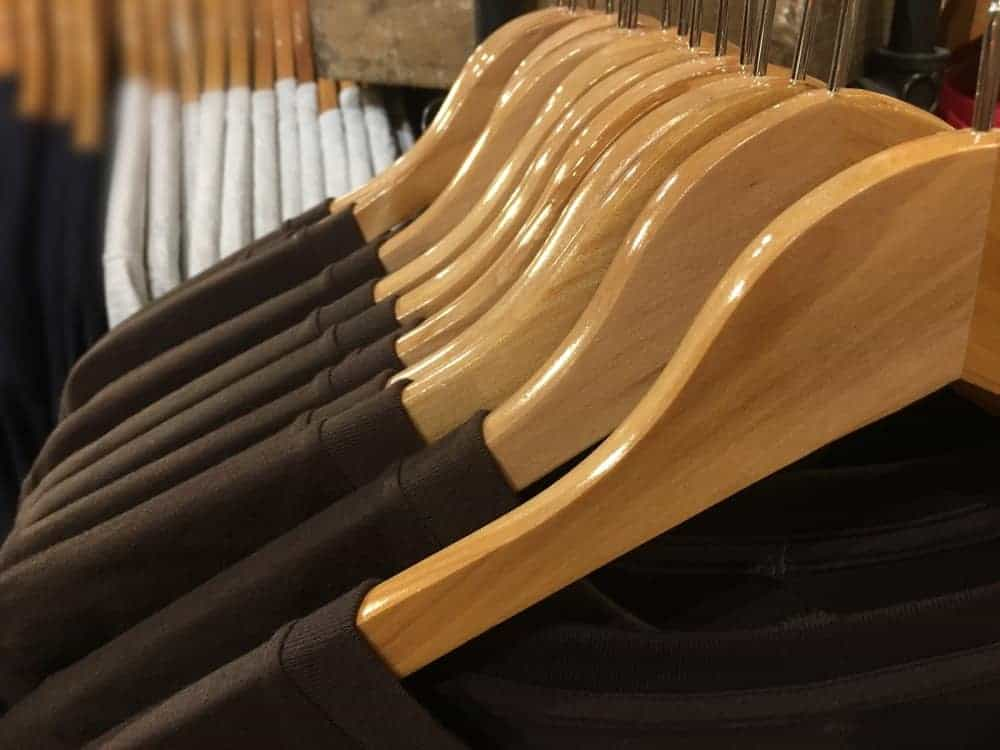 A close look at a row of wooden hangers at a store.