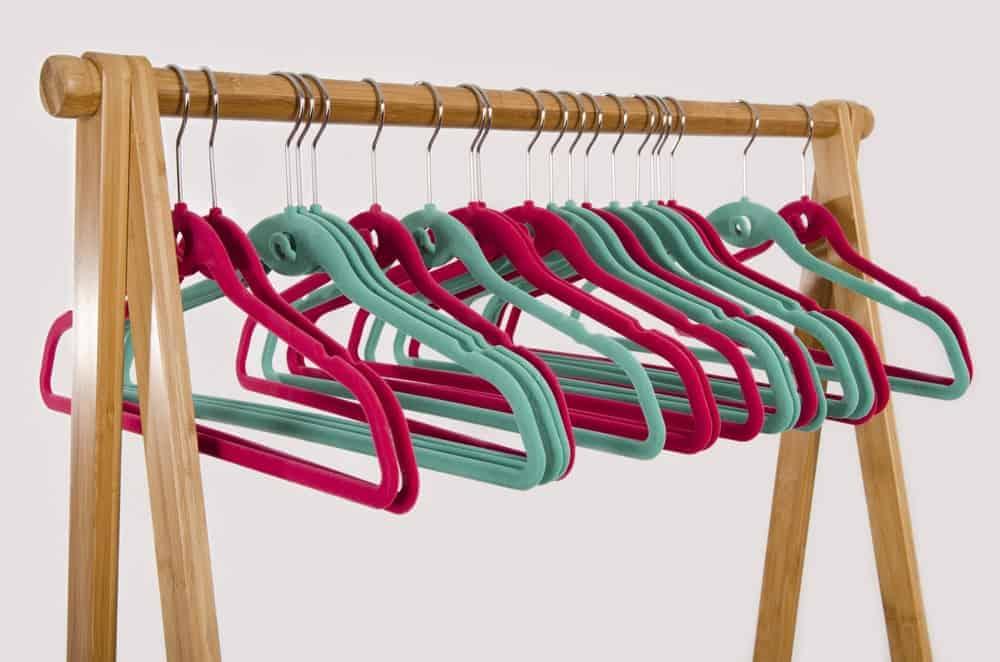 A row of velvet hangers on a wooden rack.