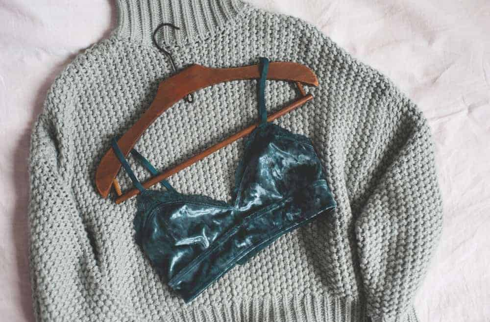 A gray sweater and a lingerie in a petite hanger.