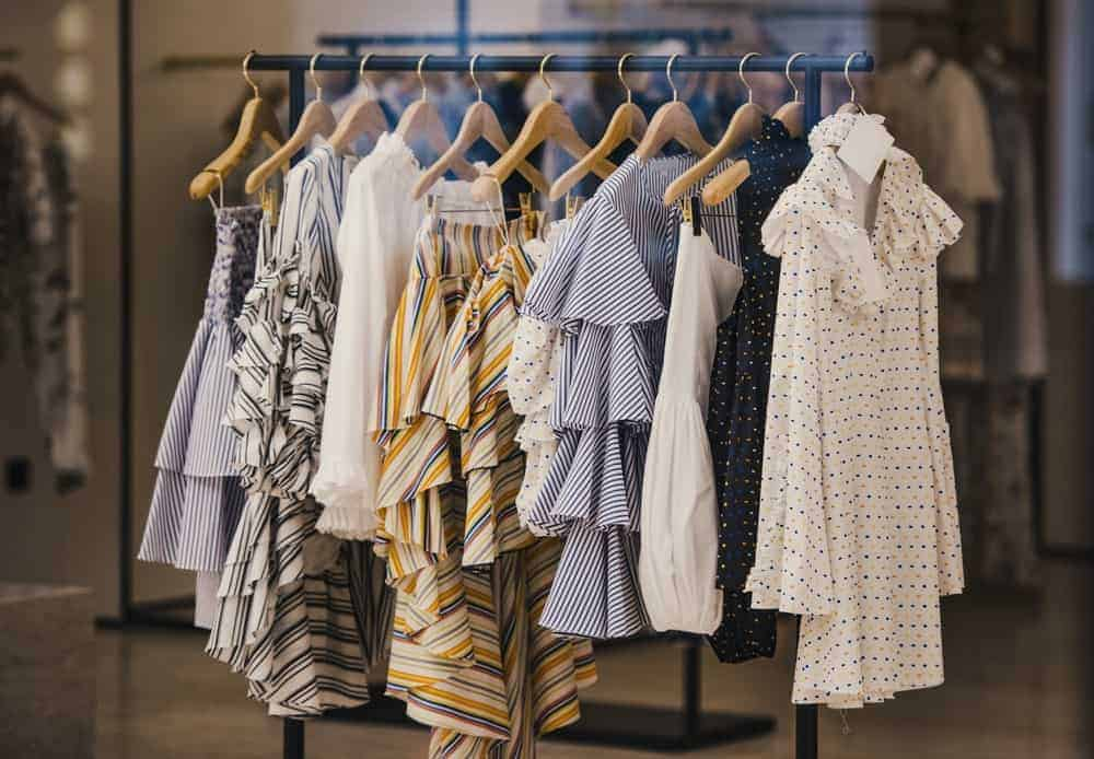 A rack of blouses supported by wooden dress hangers.