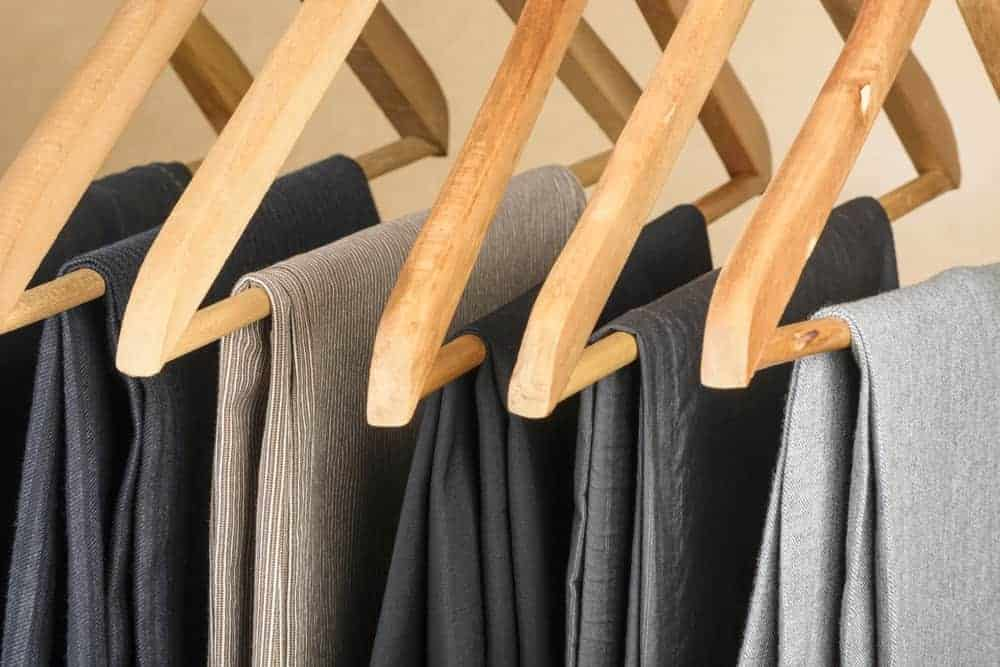 Multiple pairs of pants supported by wooden pant hangers.