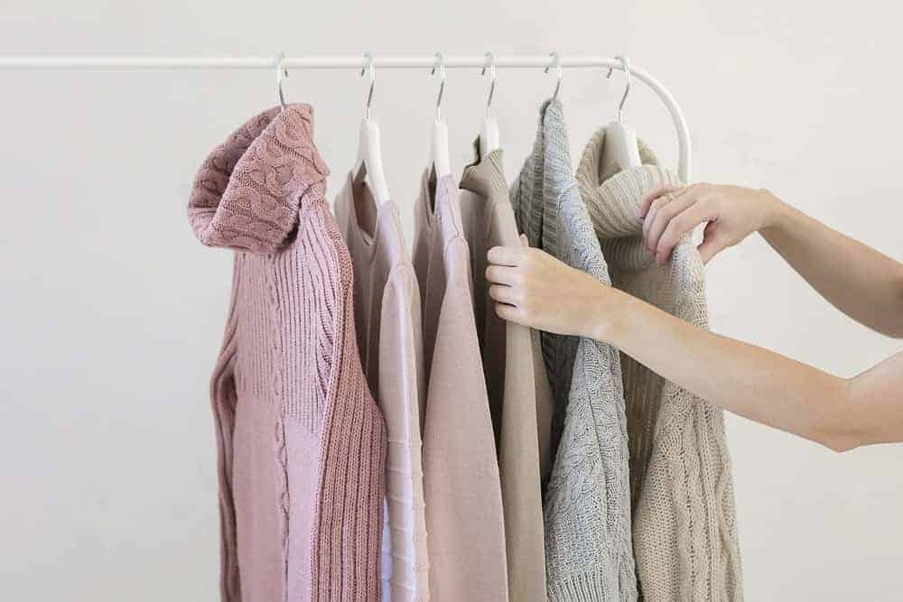 A variety of sweaters supported by sweater hangers.