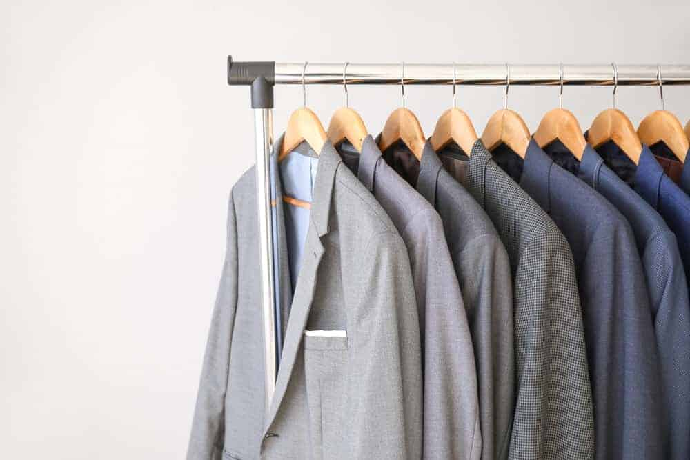 A rack of various coats supported by suit hangers.
