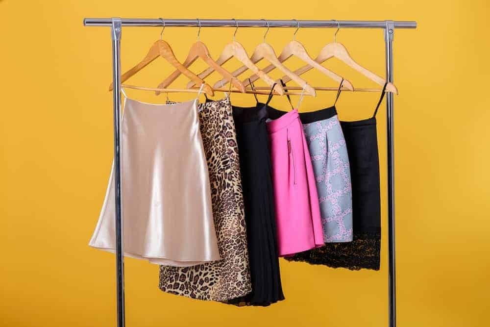 Colorful skirts hanging on wooden skirt hangers.