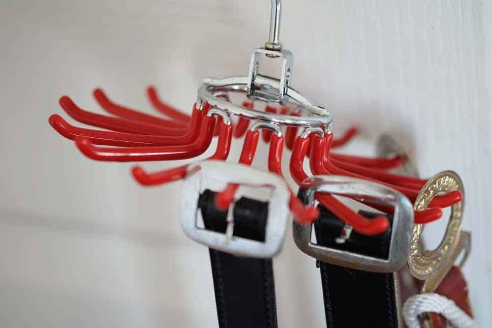 A red metal belt hanger supporting multiple belts.