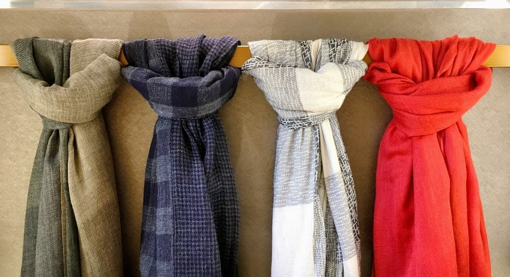 A row of scarves on a scarf hanger.