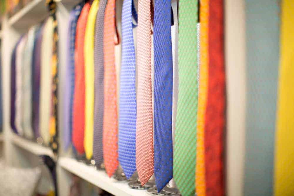 Colorful neckties on display supported by tie hangers.