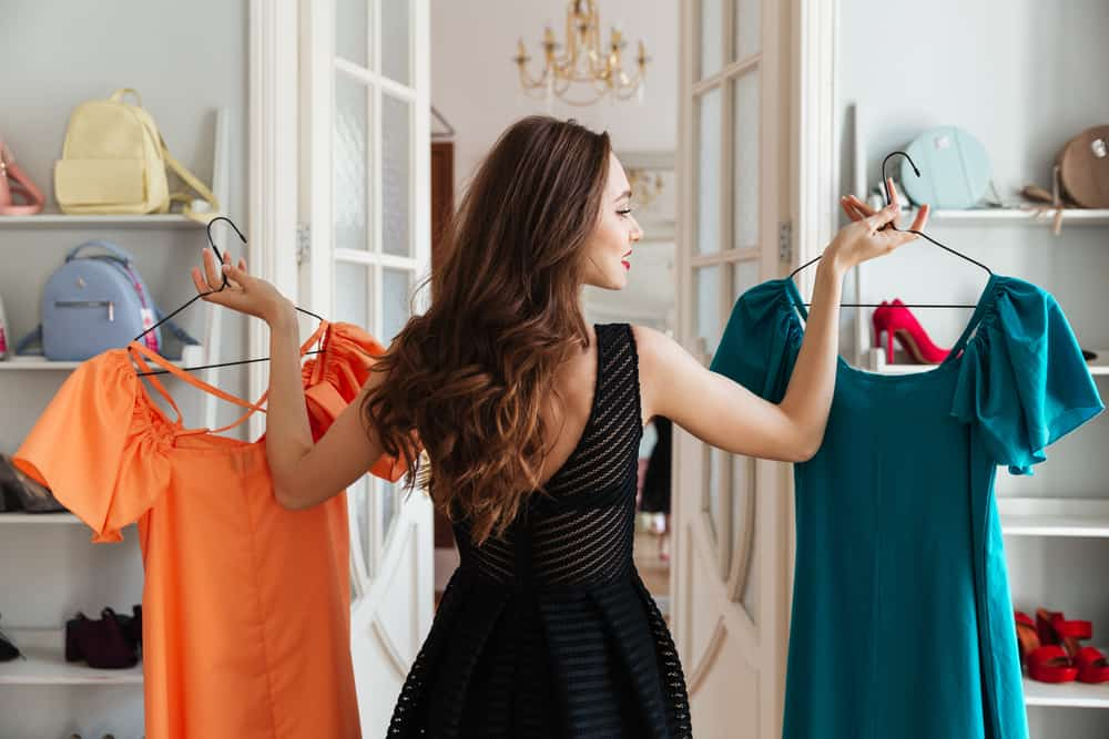 Woman in a store picking out dress.