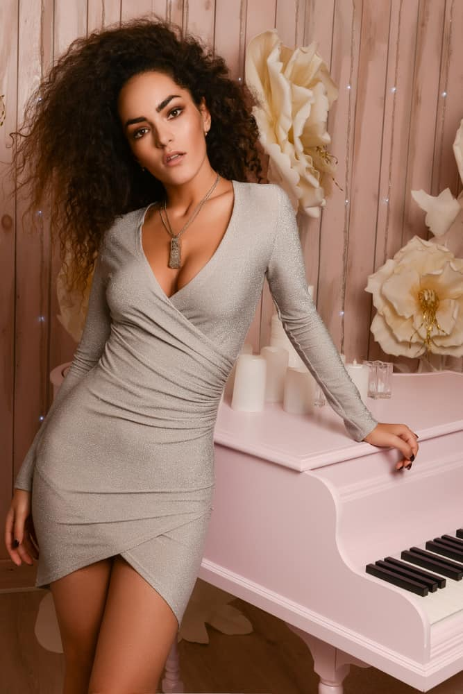 Woman in a short wrap dress standing next to a piano.