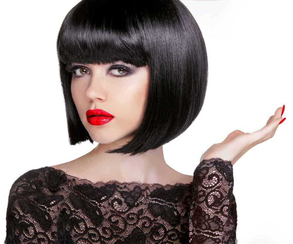 Model with black bob cut and full bangs.