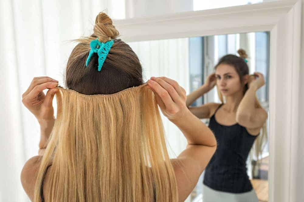 A woman putting on a blonde hair extension in front of a mirror.