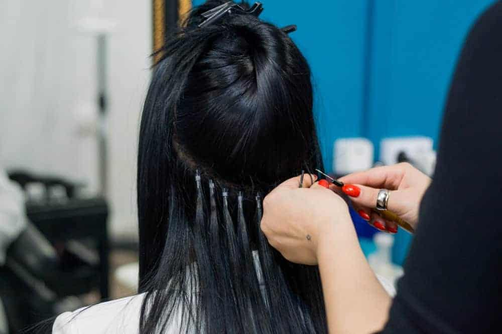Stylist applying hair extensions to a woman's black hair.