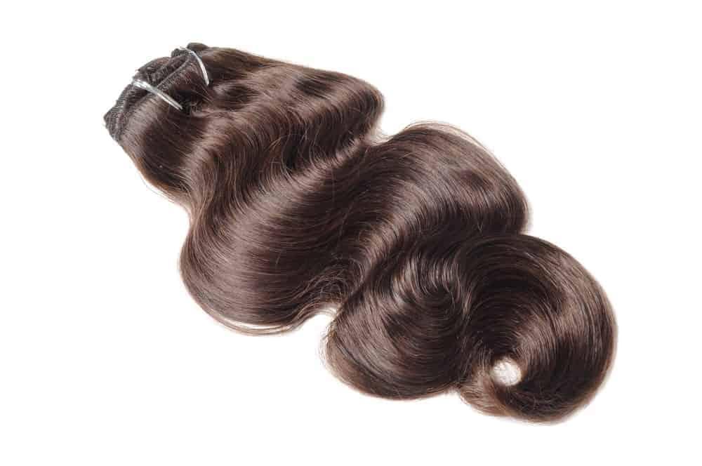 Clip-in body hair extension in wavy, dark brown.
