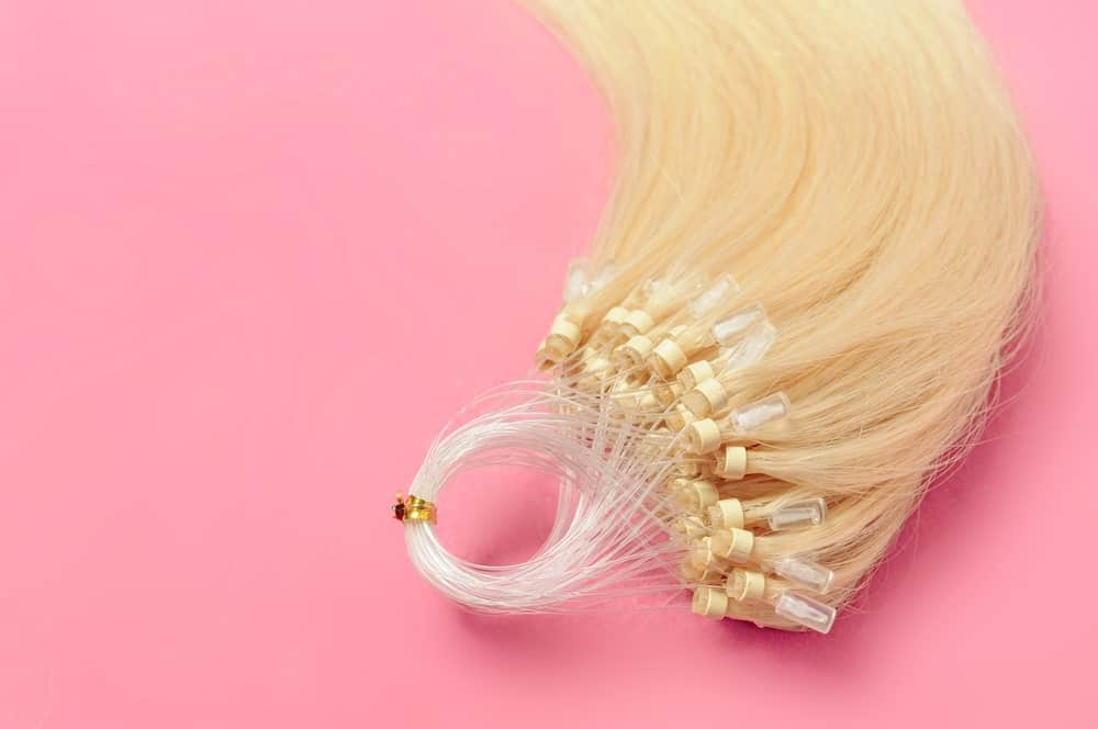 Pre-bonded straight flat human hair extensions against a pink background.