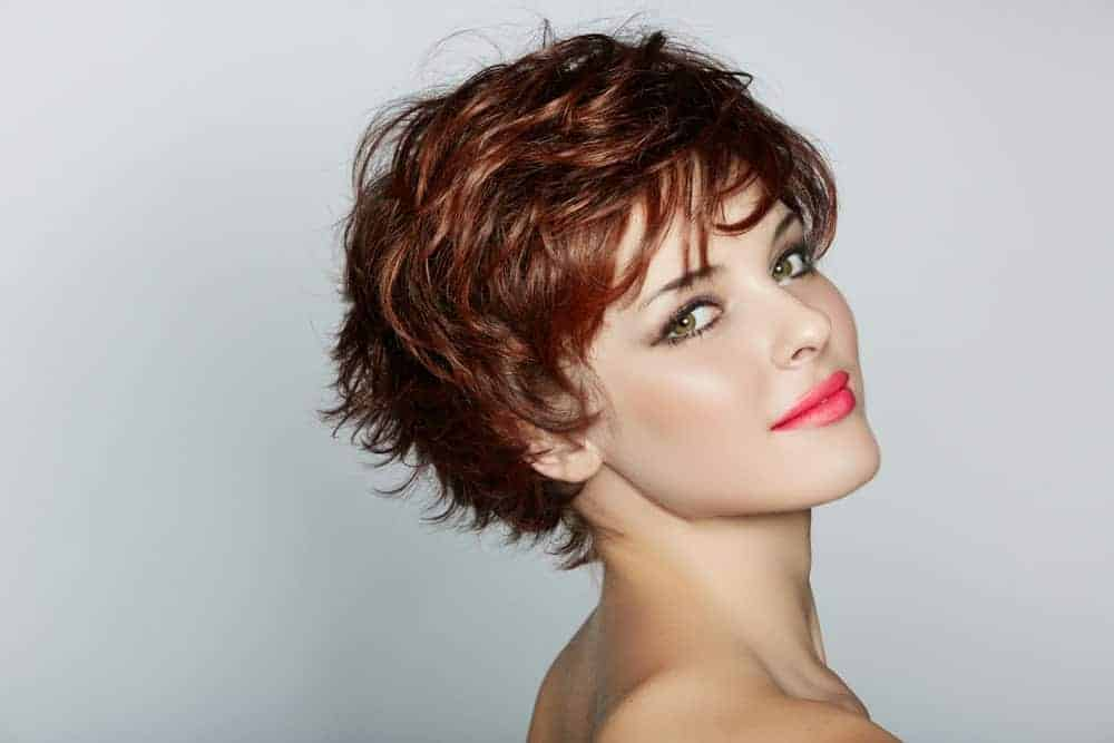 A woman wearing wearing short pixie crop wig in red shade.