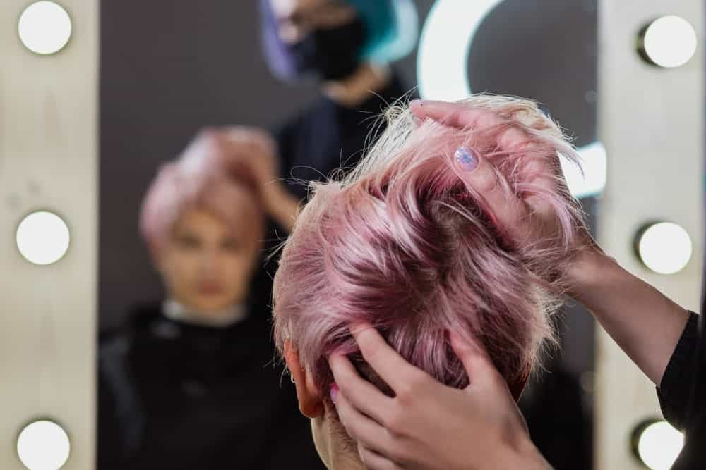 Hairdresser applying a pixie cut wig to a woman client.