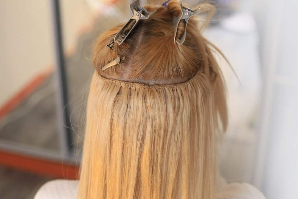 Woman's blonde hair sewn on a pigtail with hair extensions.