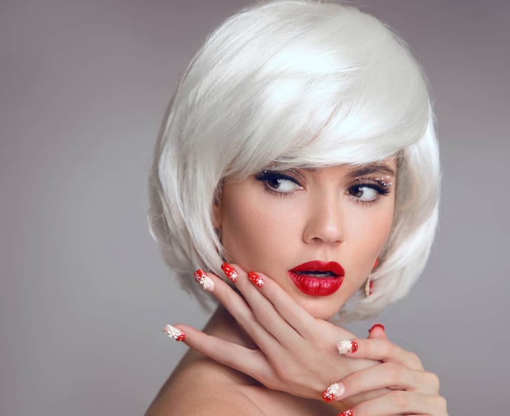 This is a woman wearing a short-haired platinum-colored wig with side-swept bangs.
