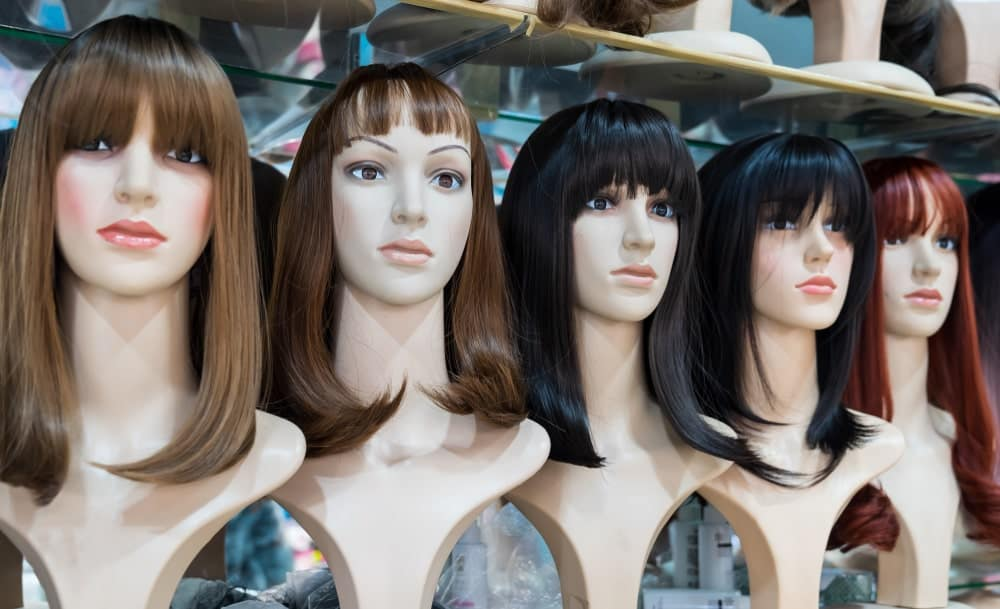 A row of various shoulder-length wigs on display.