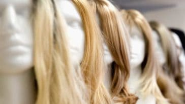 A row of long-haired wigs on display.