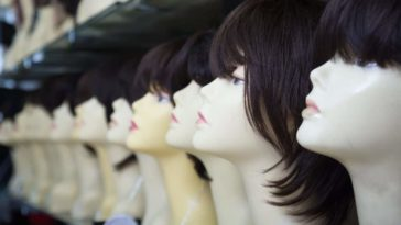 A row of wigs with bangs on display.