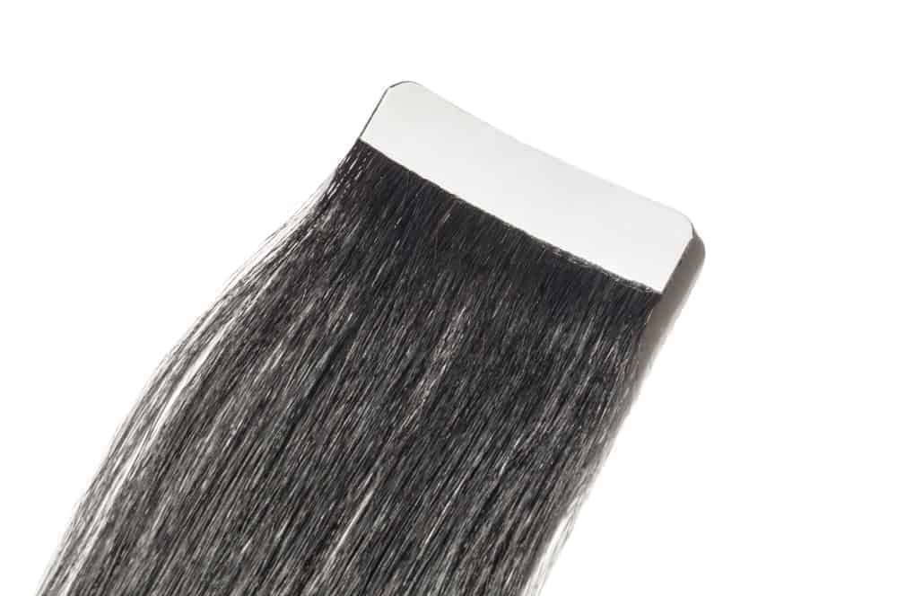 Tape in pre-bonded straight black human hair extensions.