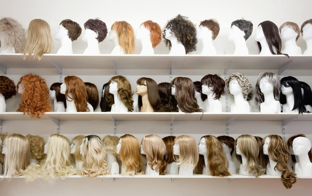 Display shelves filled with mannequin heads wearing various styles of wigs.