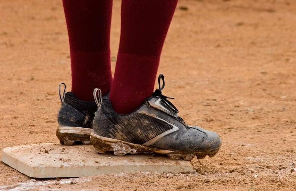 A close look at a baseball player wearing baseball shoes while standing on a base plate.