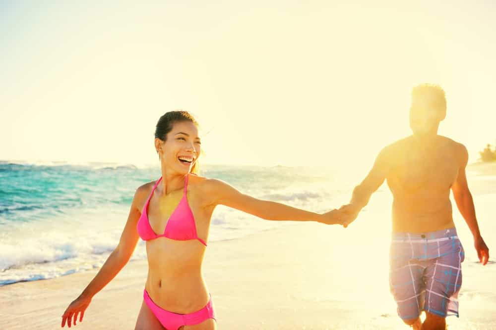 A couple wearing bathing suits at the beach.