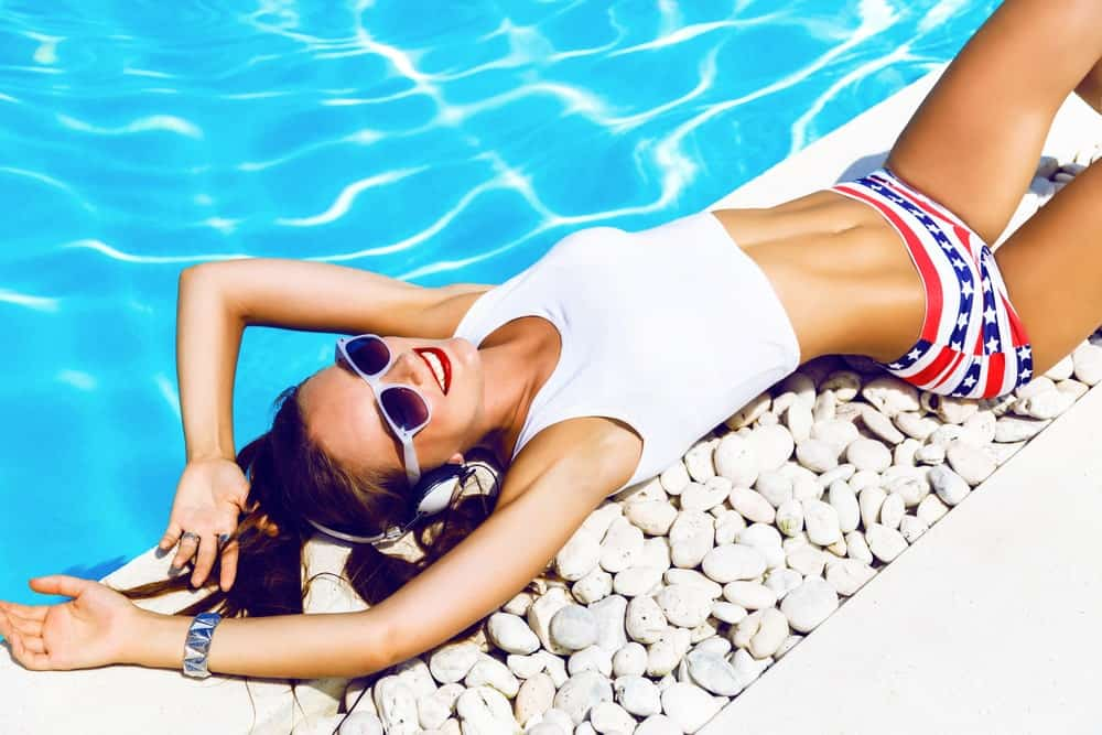 A woman wearing a white crop top swimsuit by the pool.