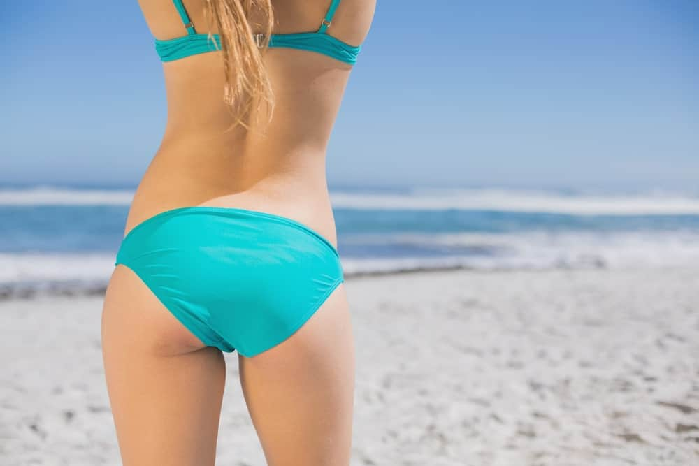 A close look at a woman wearing full coverage bottoms at the beach.