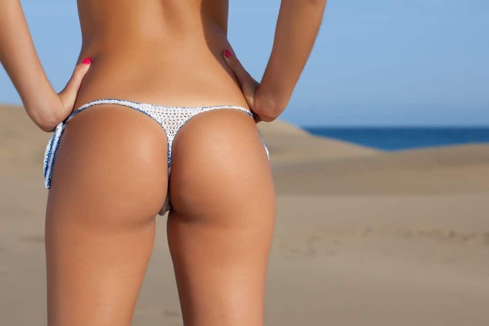 A close look at a woman wearing a thong at the beach.