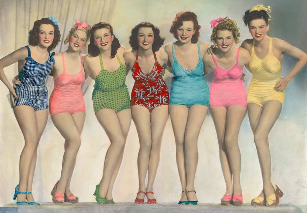 A group of women wearing classic one-piece bathing suits.