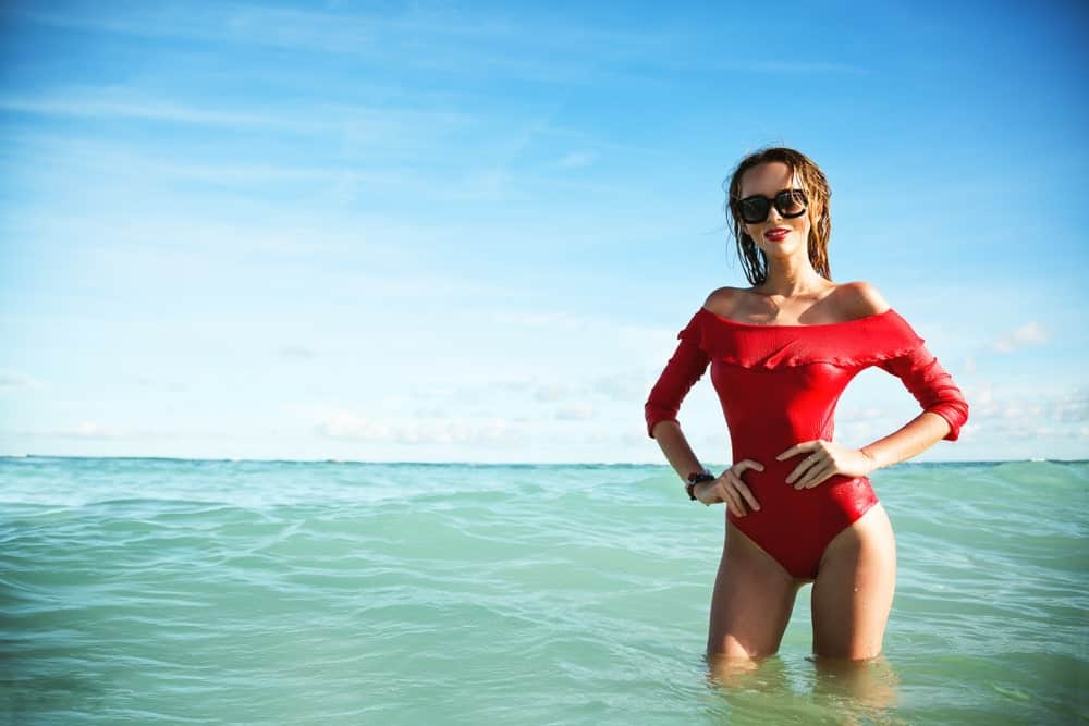 A woman posing at the beach wearing a red swim dress.