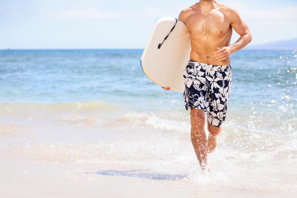 A surfer wearing floral board shorts at the beach.