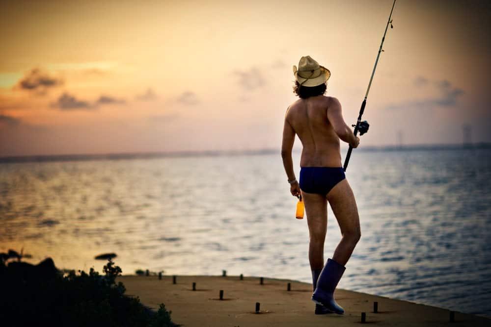 A man wearing speedos fishing.