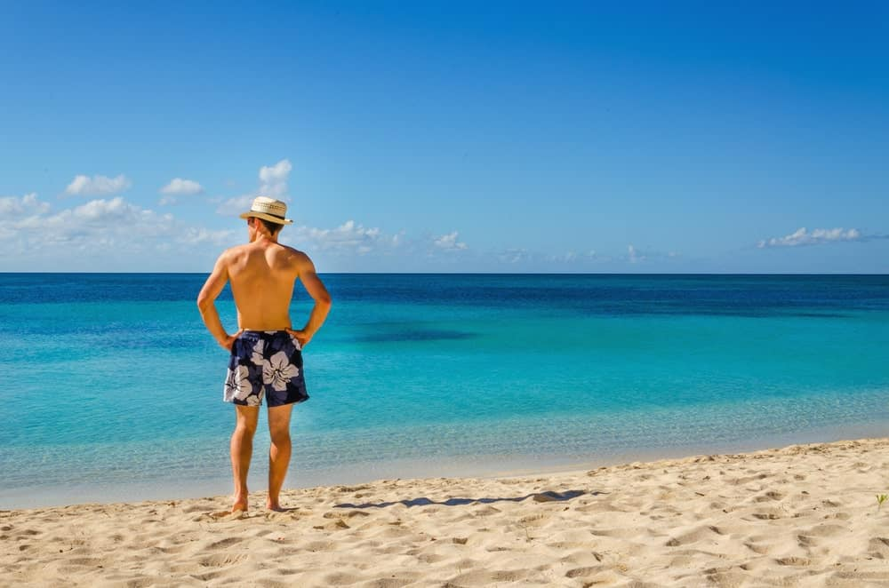 A man wearing a pair of floral swimming trunks at the beach.