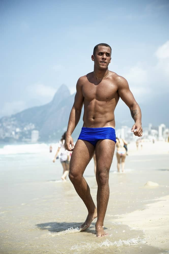 A man wearing blue swim briefs at the beach.